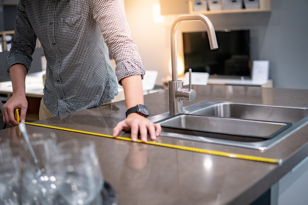 This is a close look at a man measuring the width of the kitchen island with a tape measure.