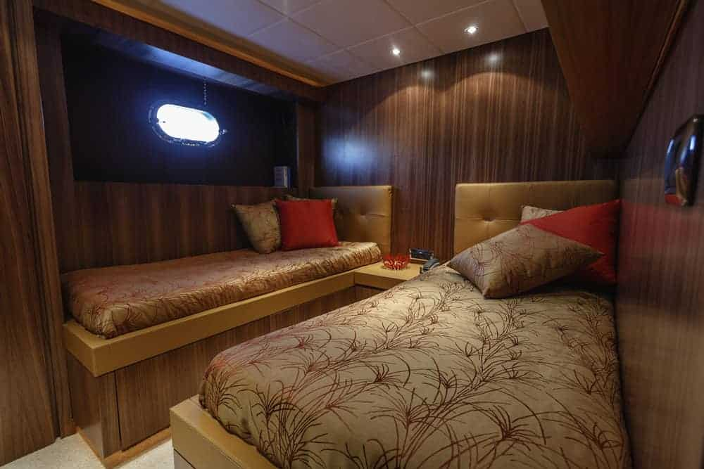 guest bedroom on yacht with two beds