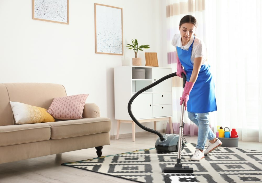 A woman vacuuming the patterned area rug in the living room.