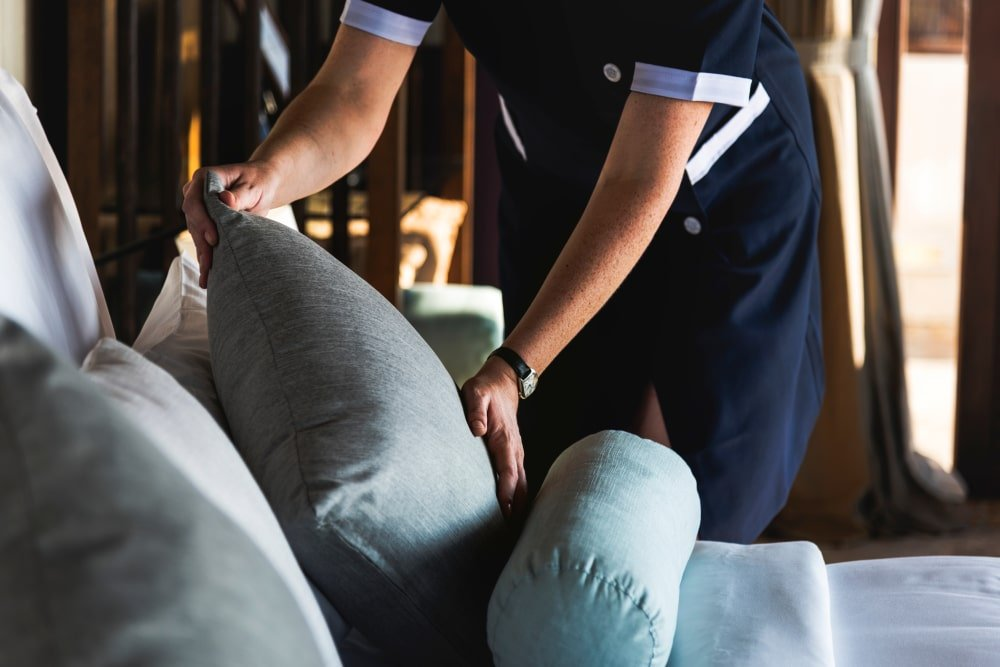 A housekeeping attendant keeping the pillows tidy.