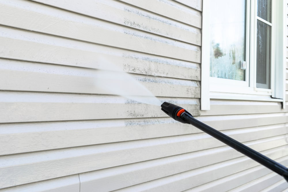 A close look at the house exterior being cleaned with a power washer.