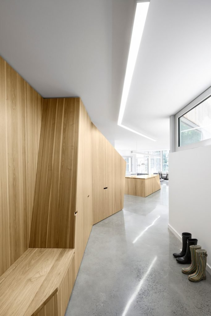 The house's entry showcases a wooden wall with built-in storage and bench over concrete flooring.