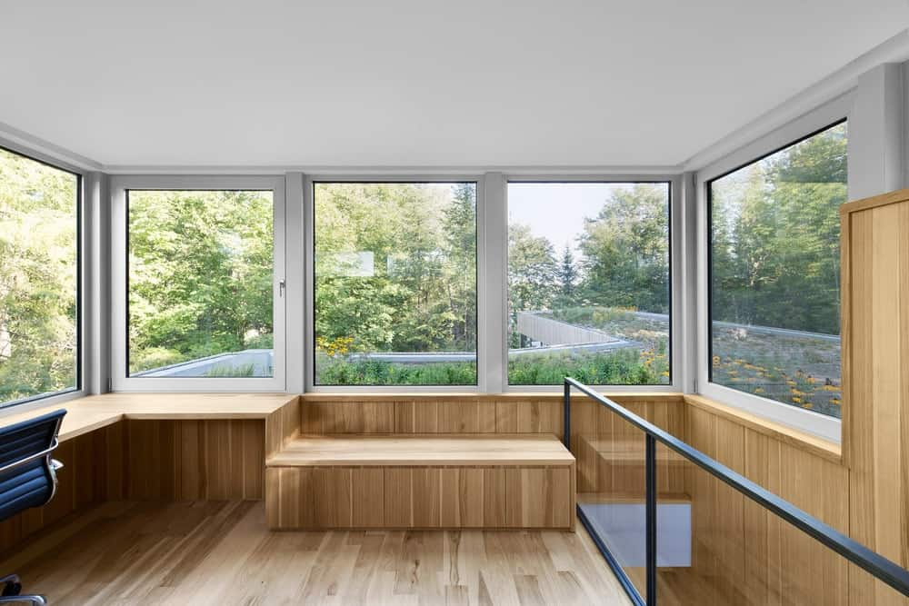 The home office is located on the rooftop of the house featuring hardwood built and glass windows.