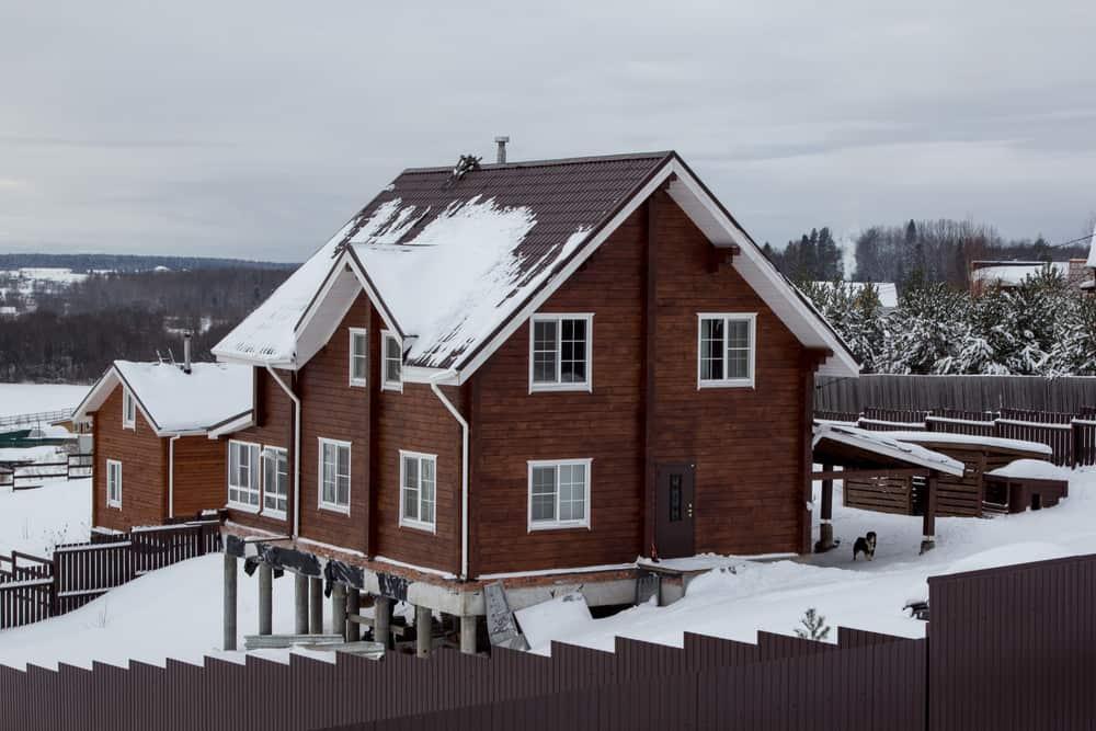Ski chalet built on stilts rising above the heavy snow-pack.