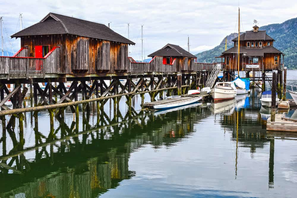 3 homes built on a long pier in harbor. Homes made entirely of wood. Fishing boats surround the homes.