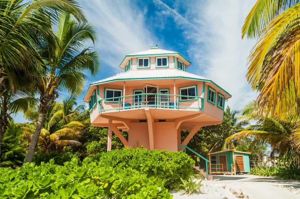 Pedestal home built high above the ground almost like a tree house on the beach surrounded by palm trees.