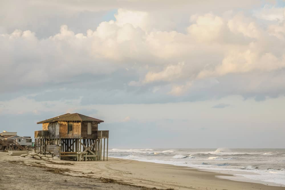 Lone beach house built close to crashing waves on the eastern seaboard in the United States.
