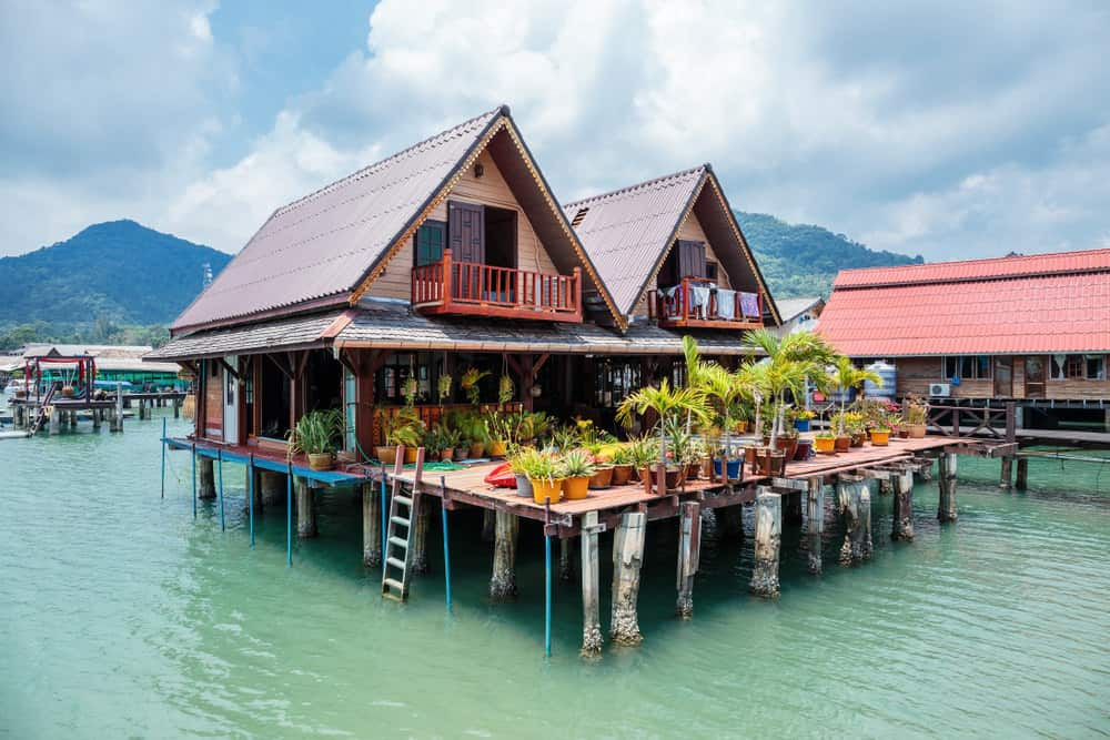 Large house in Asia built entirely on stilts and large platform with a large deck. Ladder drops down from deck to access boats.