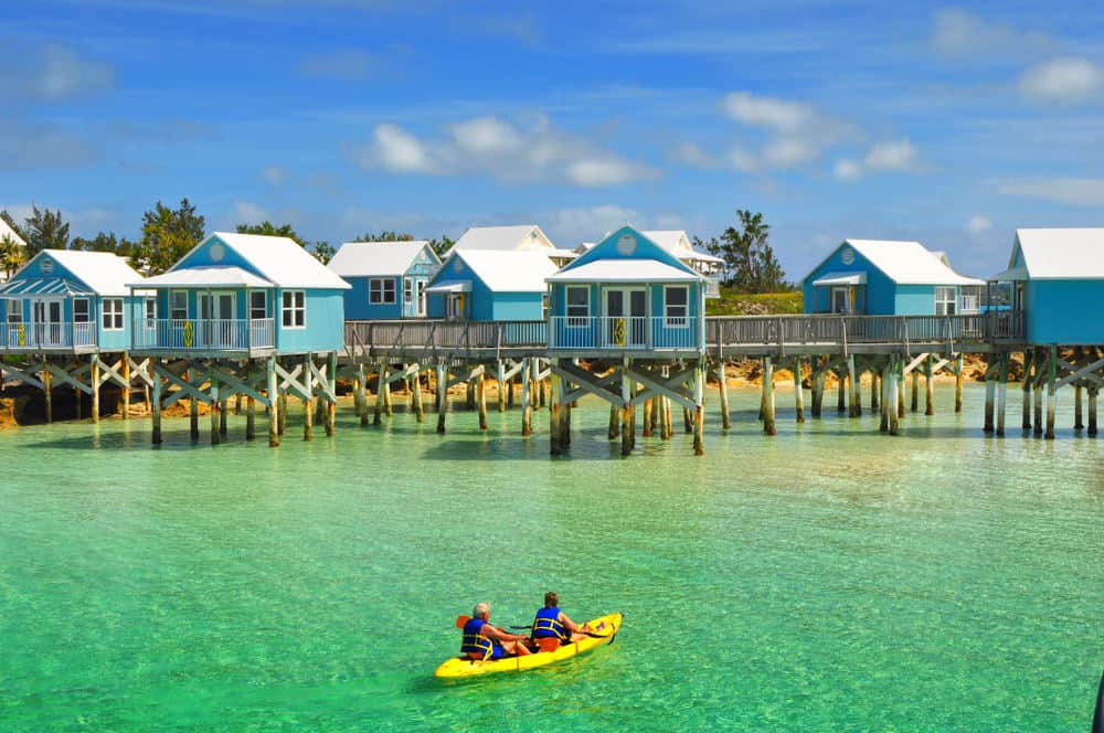 entire neigborhood of homes built on stilts over the water in tropical area.