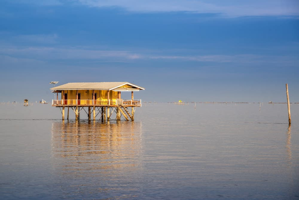 House built on stilts and platform in the middle of the water. True waterfront property.