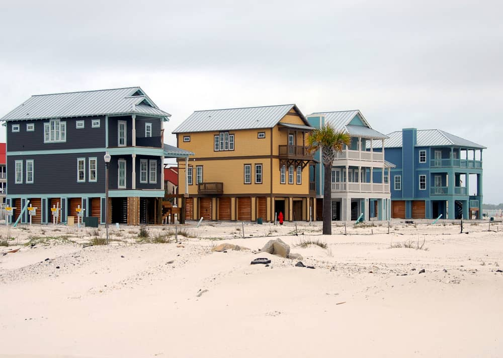 Row of large beach houses built on the sand upon stilts - elevated to protect against tide and storms.