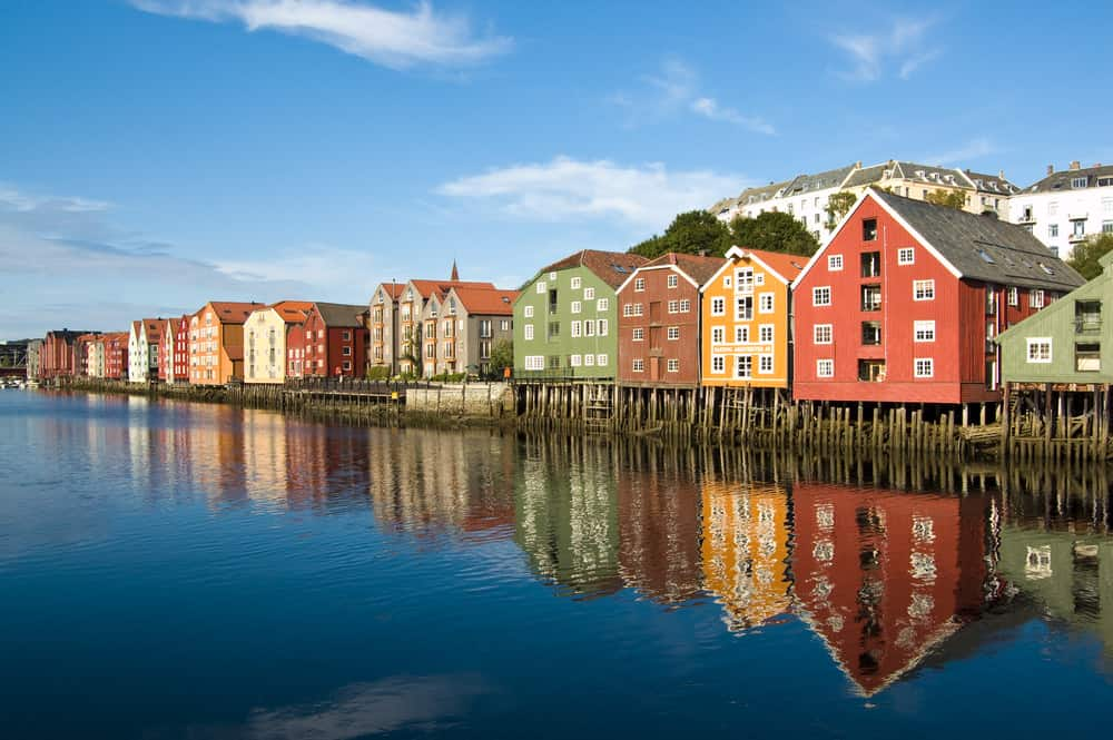 Long row of colorful homes in Norway built on pilings on the water.