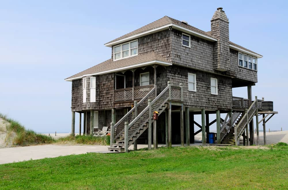 Two-story shingle siding beach house built up on support stilts.