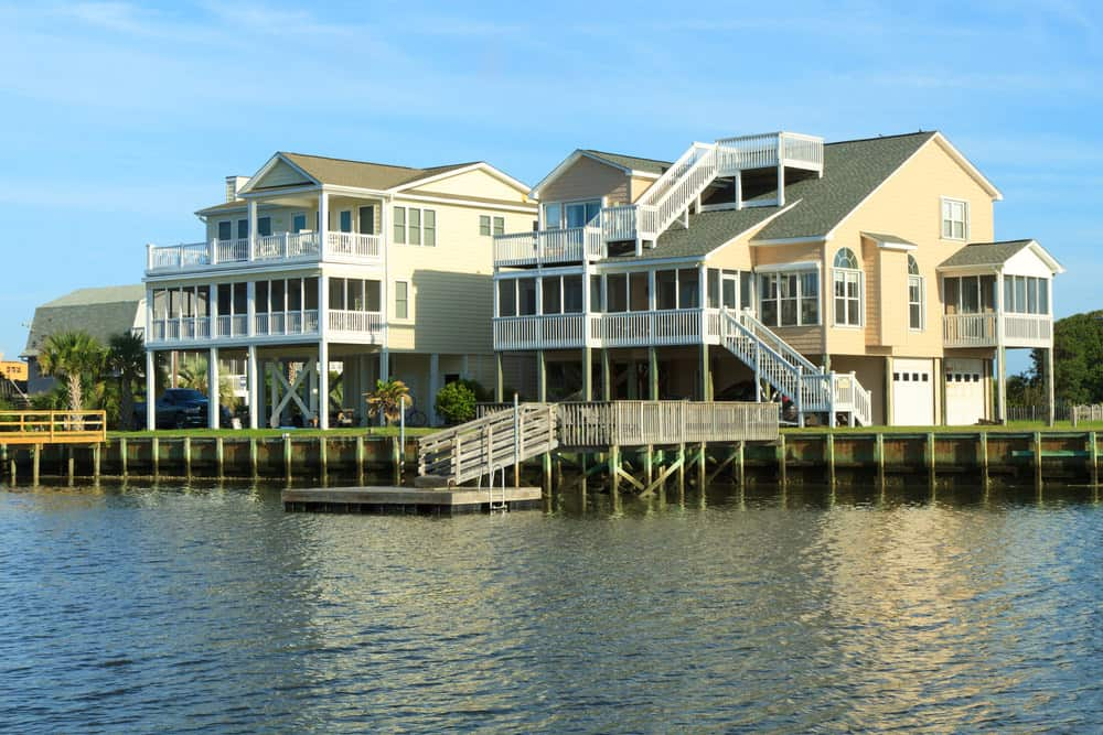 Two luxurious waterfront homes built on pilings over the water in the USA.