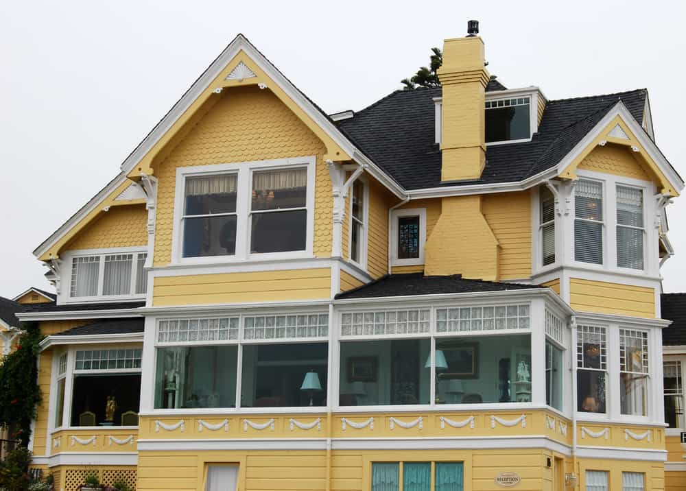 Large yellow Victorian style home with intricate white trim contrasted nicely with charcoal grey roof shingles. Chimney is yellow as well.