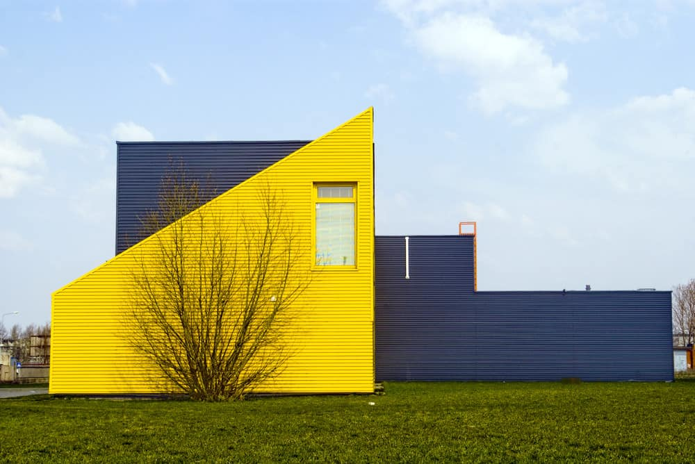 Ultra modern yellow and dark gray home with sharp triangle geometric design on a minimalist landscaping.