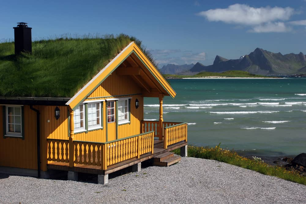 Orange yellow beach cabin with grass roof and front deck on the beach in Scandinavia.