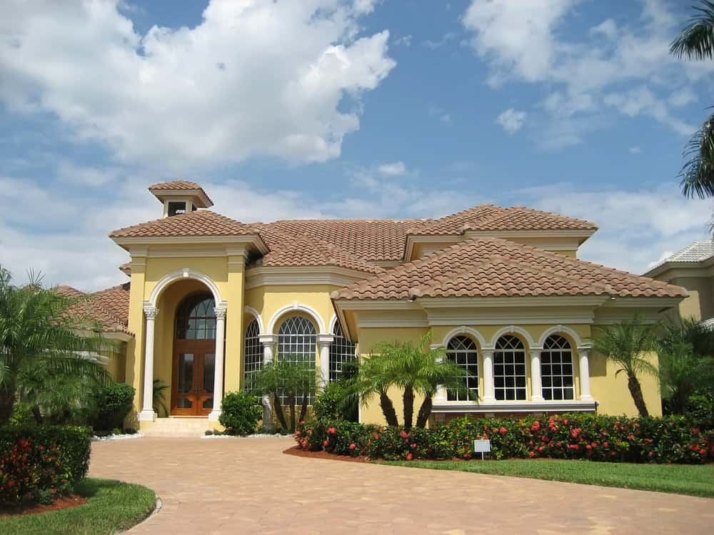 Yellow, one story Mediterranean style home with arched front door portico and arched front windows. Windy brick walkway leads to front door.