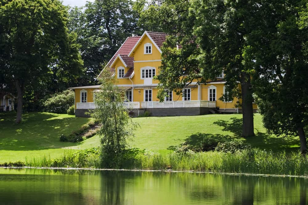 Stunning large yellow lake house on huge property with sloping lawn to the lake surrounded by mature trees. The home has white trim and red shingle roof. Absolutely stunning.