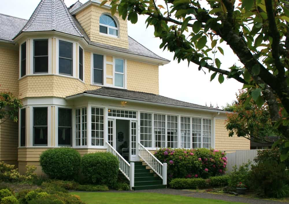 Another yellow victorian style home with wide enclosed porch.