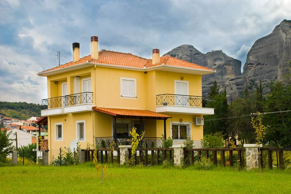 Sharp yellow home in continental Europe with red roof with view of majestic mountains.