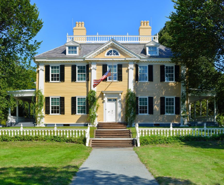 Stunning yellow New England home with white picket fence, black exterior shutters, white door flanked by mature trees.