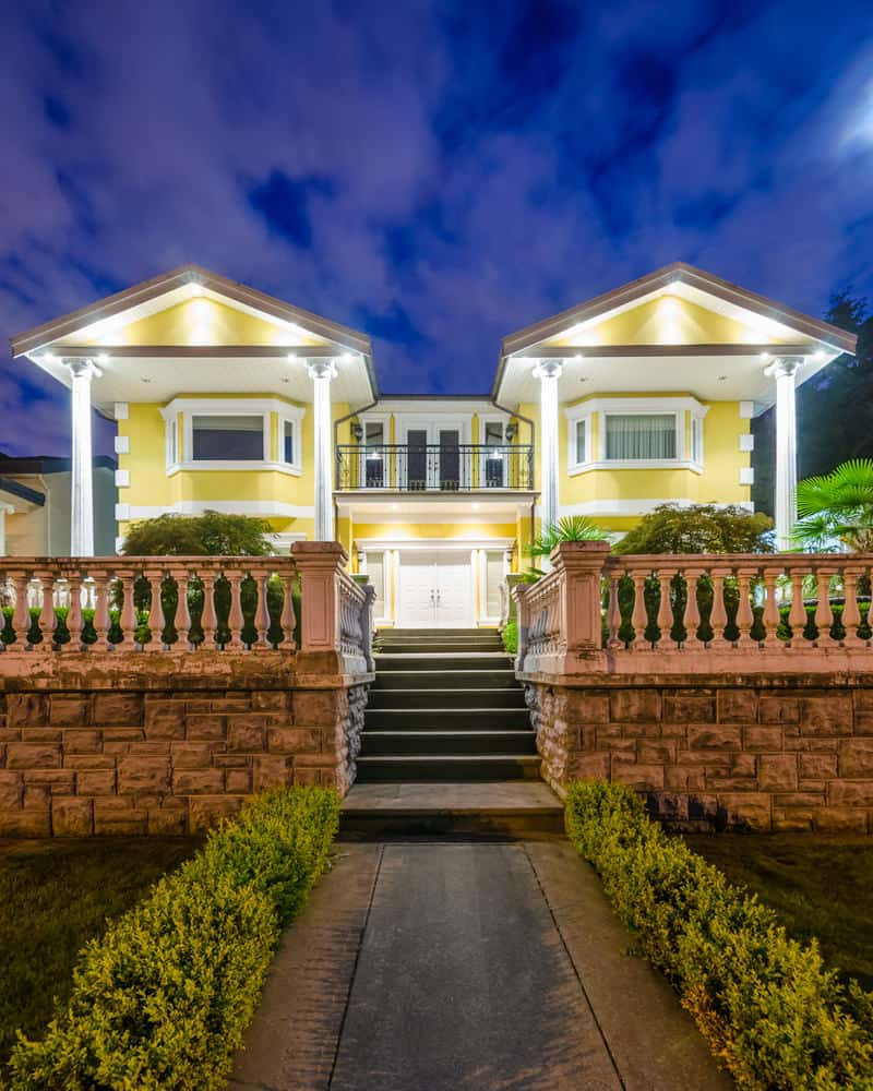 Luxury yellow mansion up on a hill at night with double white front door.