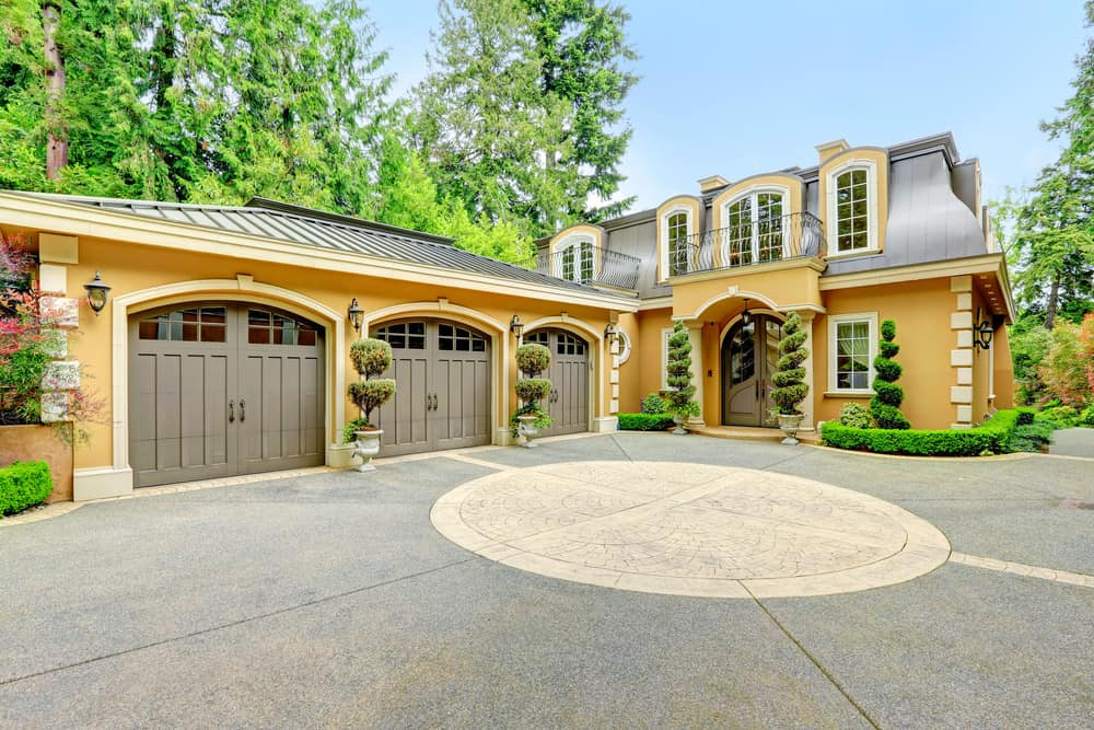 Stunning French style beige/yellow home with three car carriage style garage.