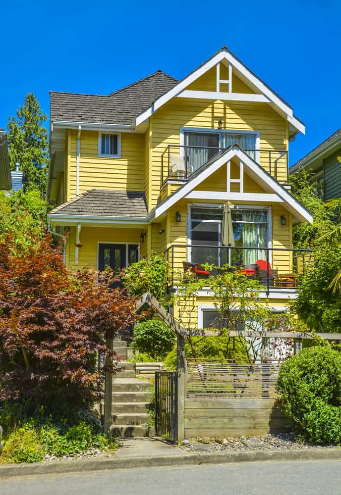 Beautiful narrow Victorian style yellow home in Vancouver, BC with wide stairs to front door. Gables have front-facing white trim.
