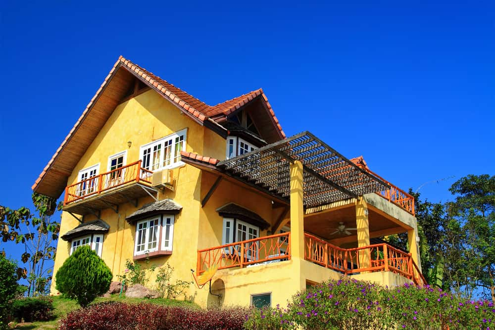Large old yellow home with balcony and large deck. Deck railing is red contrasting nicely with the strong yellow color.