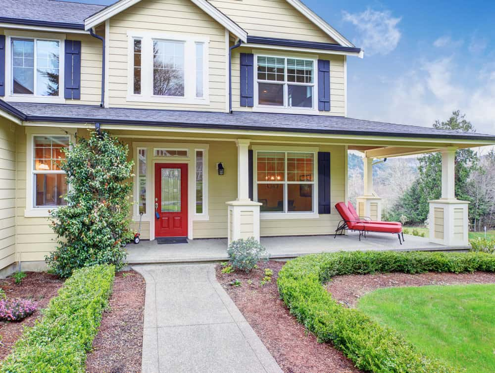 Very soft yellow, almost white home with broad porch and red door. Black shutters frame the windows.