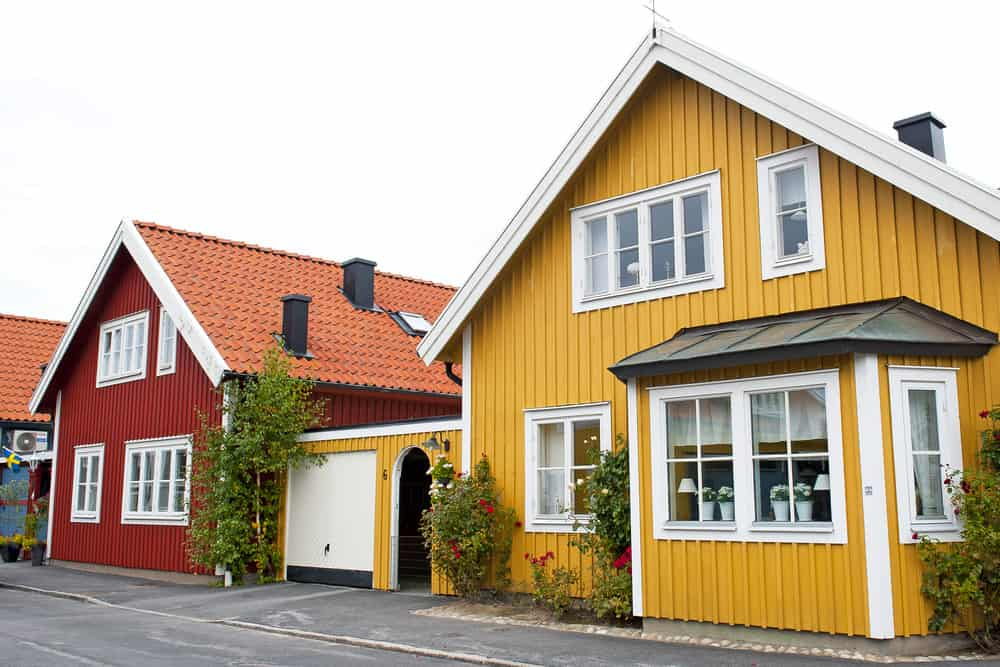 Old village yellow house in Sweden with white trim and small garage next to classic red Swedish house.