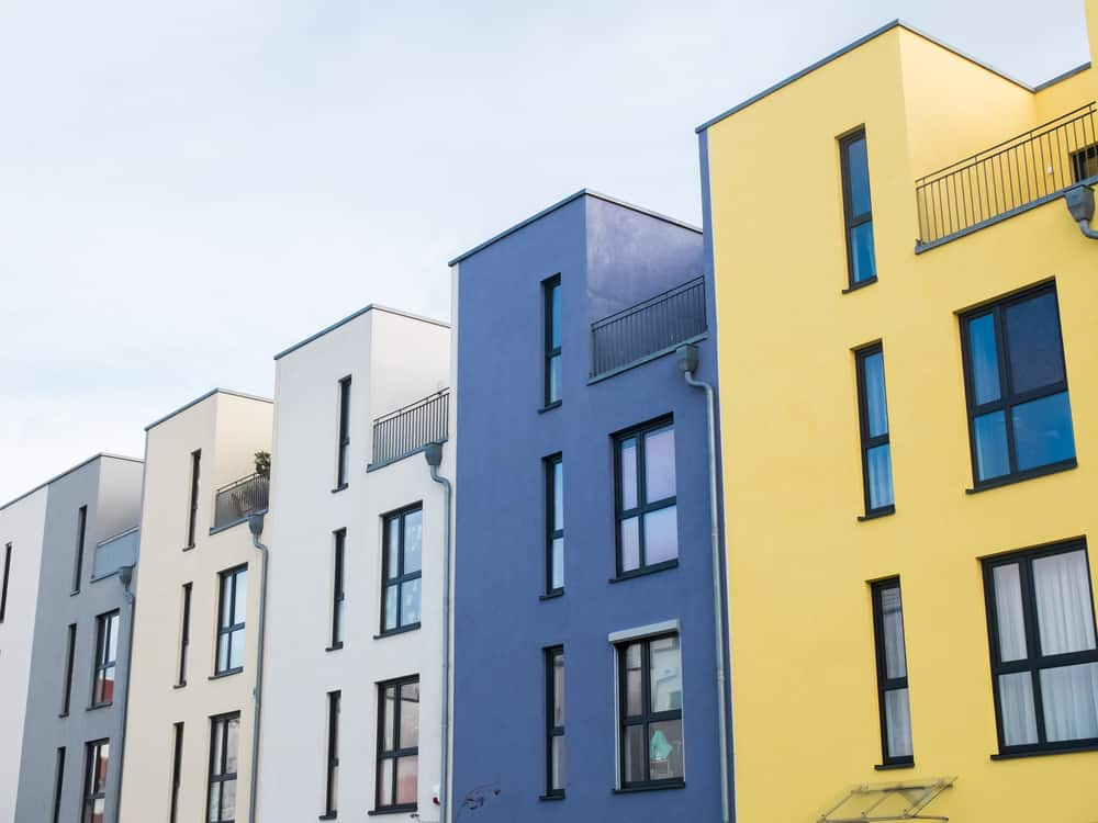 Row of modern townhouses - white, blue and yellow.