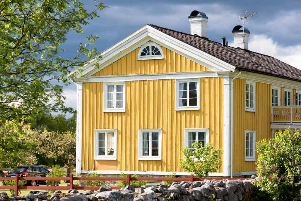 Classic Swedish house in yellow with white trim. This is a beautiful yellow home in the country with gabled roof topped with two white chimneys.