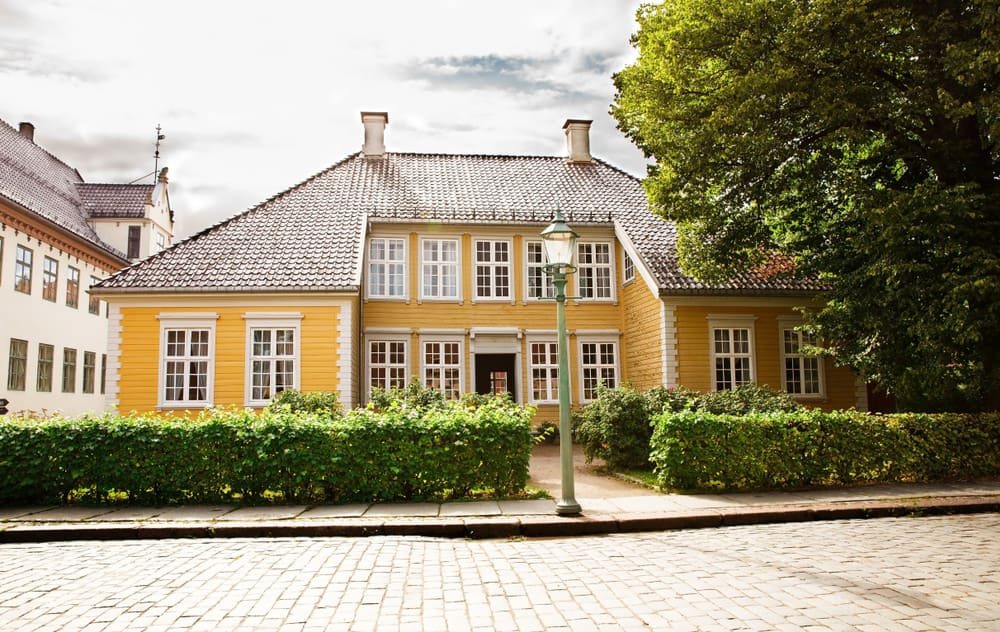 Large unique yellow old home in Norway with long sloping roof, two chimneys and white trim on the many windows. Nice box low box hedge in front yard.