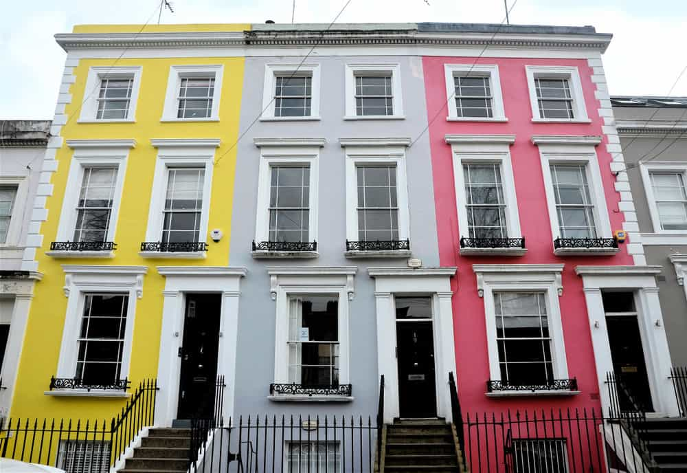 Row of three townouses - yellow, gray and pink. 3 stories; narrow design. Very colorful. Attractive row houses.