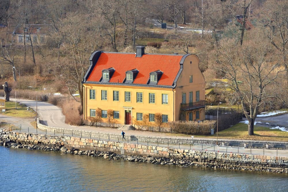 Old yellow country home in Sweden with red roof. Classic symmetry with this 3 story large home on the water.