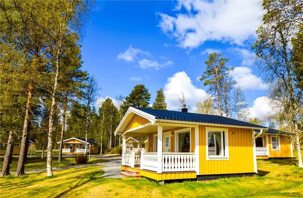 Small one story yellow cabin with small front porch in the country and slight gabled roof.