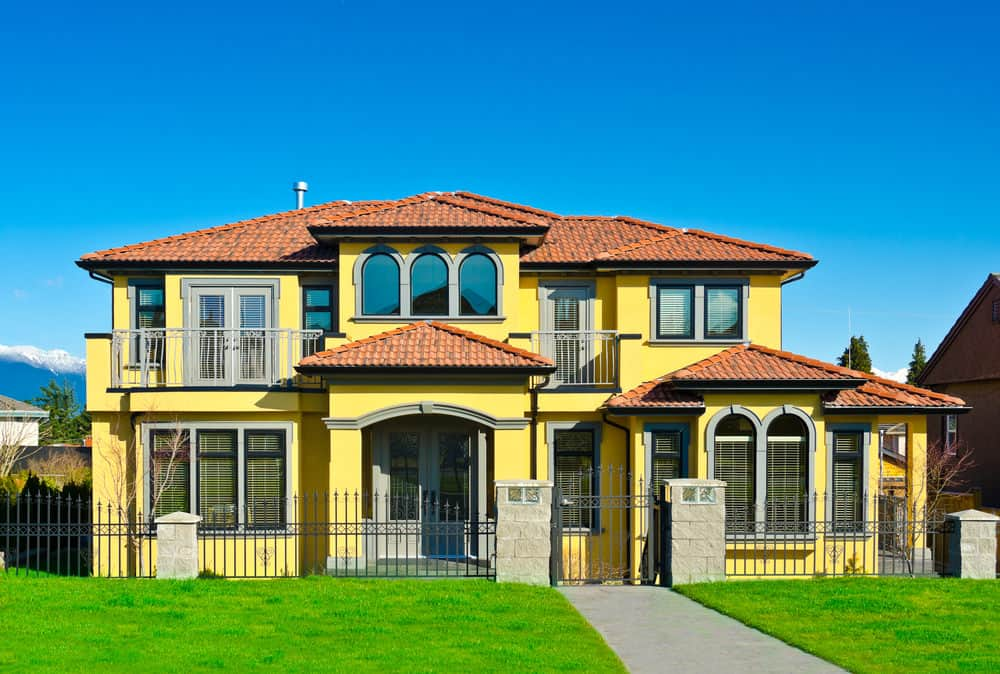 Yellow Mediterranean style home with red tile roof in Vancouver, BC.