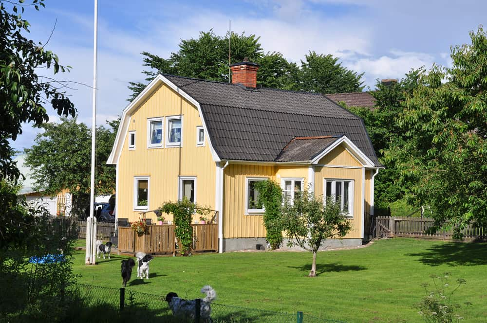 Old gambrel roof yellow house in Sweden on large country lot with white trim.