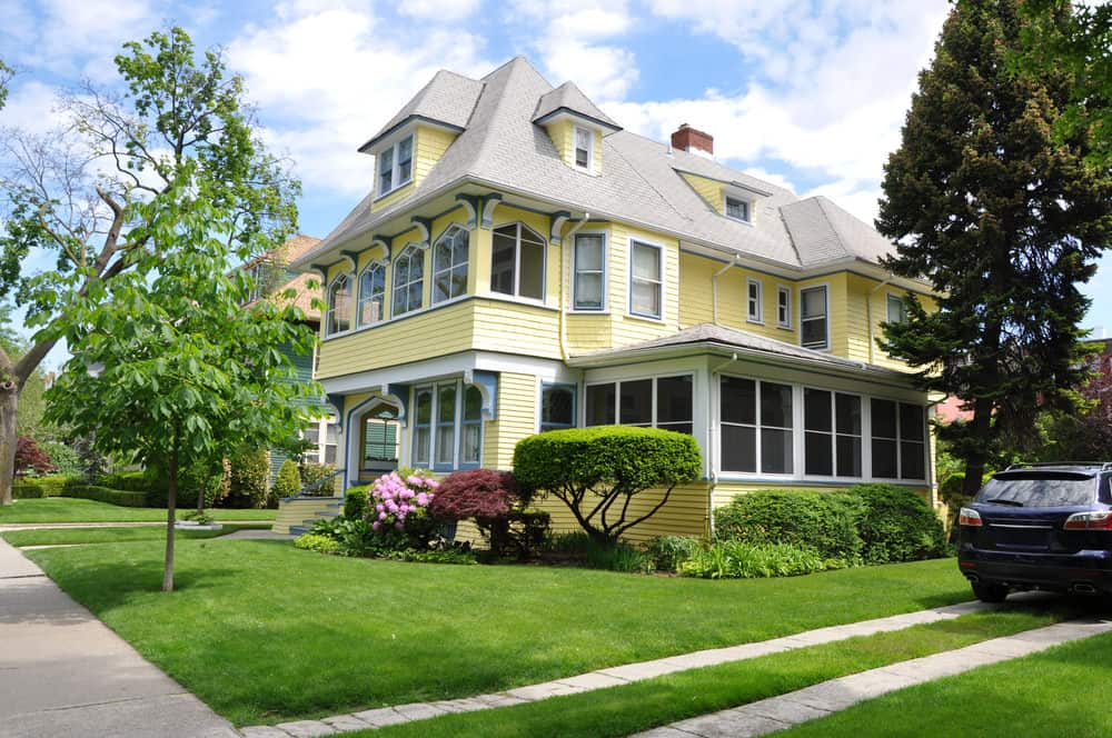 Beautiful Victorian yellow home with enclosed front porch surrounded by lovely gardens. The yellow offset by green and white trim and light gray roof.