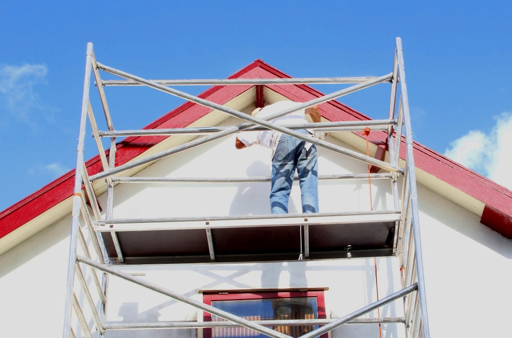 A close look at a worker painting the exterior walls of the house.