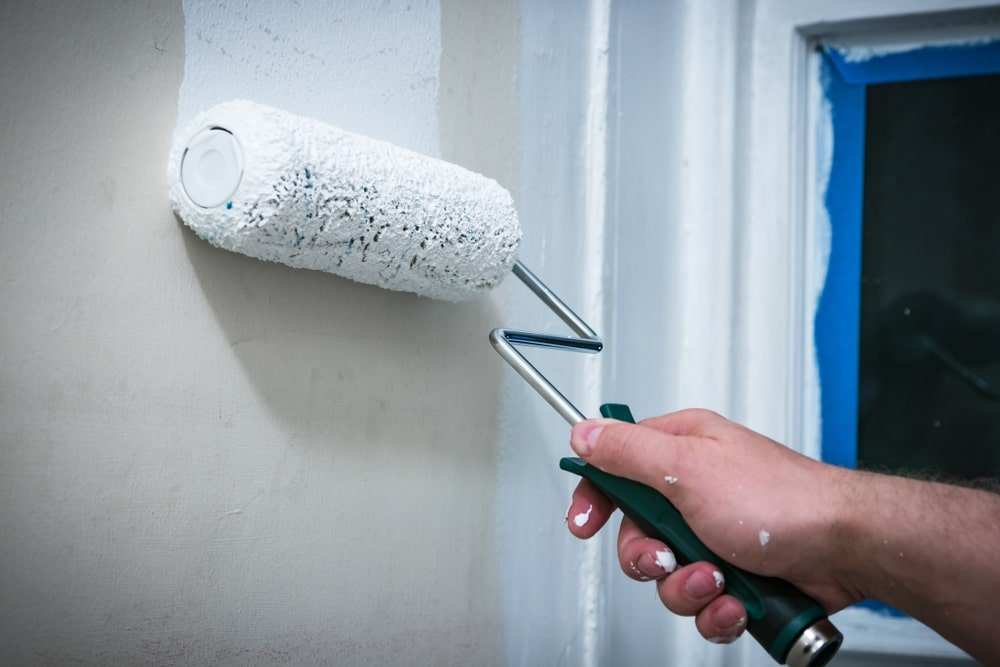 A close look at a man applying primer paint on the interior wall.