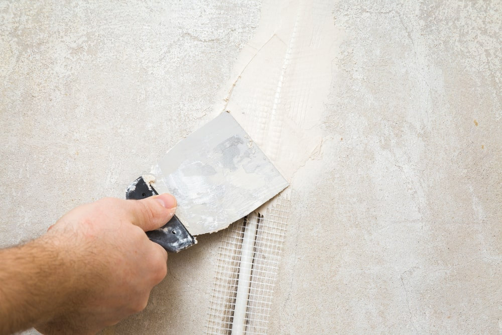 An electric wire hole being repaired with wall putty.