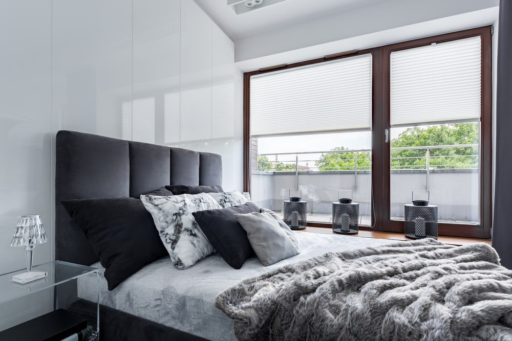 A modern white bedroom with a glossy white finish on the wall behind the headboard.