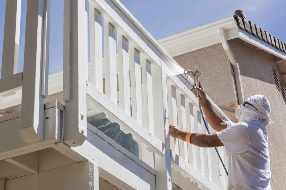 A professional house painter spray painting the balcony railings.