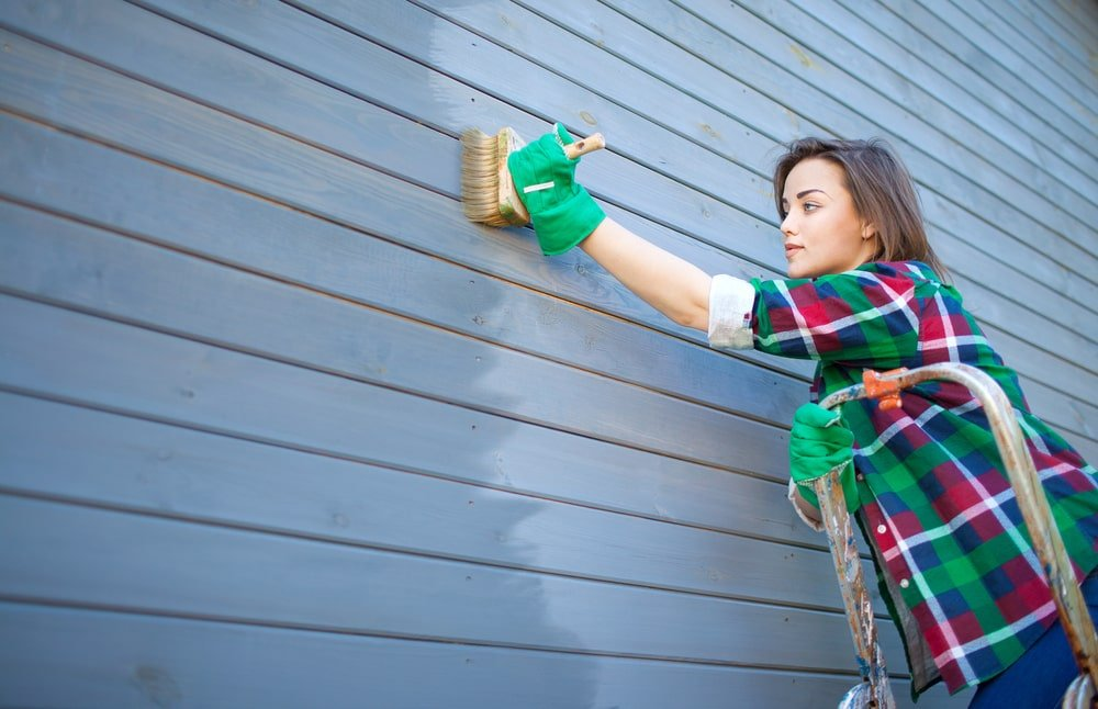 A close look at a woman applying protective varnish to the exterior walls of the house.