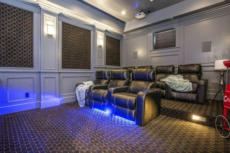 The house offers stylish home theater with sectional theater seats and carpet flooring.