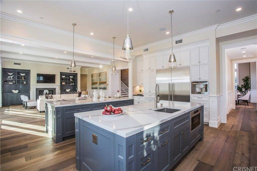 Another look of the kitchen featuring two large center islands and perfectly-placed lighting.
