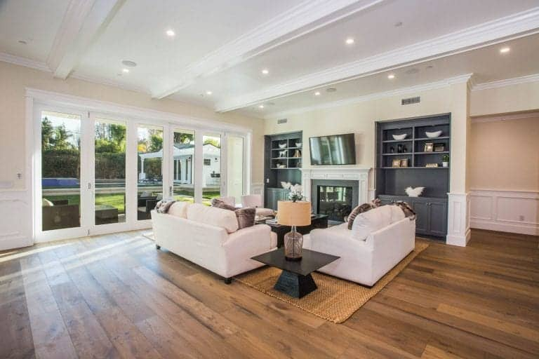 An expansive living room with full height glazing and wood plank flooring topped by a woven rug. It has gray built-in shelving and cabinets with television and fireplace in the middle.